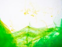 Stäng sig upp på dissippation för guling-gräsplan akrylfärgpulver i flytande Två små droppar av färgpulver som upplöser in i vatt arkivfoton