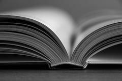 Stäng sig upp på en öppen bok i svartvitt arkivfoton