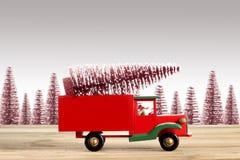 Stäng sig upp på en leksakbil med julgranen på grå bakgrund med kopieringsutrymme royaltyfria bilder