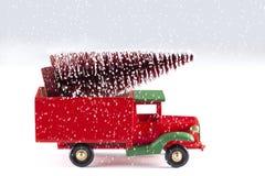 Stäng sig upp på en leksakbil med julgranen och snöflingor som isoleras på vit bakgrund arkivfoto