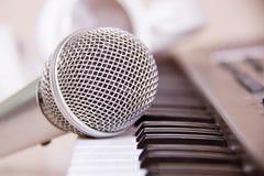 Stäng sig upp på en mikrofon under inspelningperioden med en sångare, pianot i bakgrunden, musikstudio Royaltyfri Bild