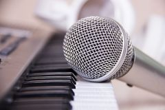 Stäng sig upp på en mikrofon under inspelningperioden med en sångare, pianot i bakgrunden, musikstudio Arkivbild