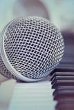 Stäng sig upp på en mikrofon under inspelningperioden med en sångare, pianot i bakgrunden, musikstudio Fotografering för Bildbyråer
