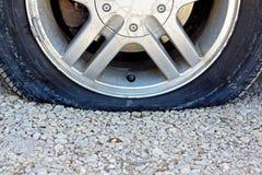 Stäng sig upp på gummihjulet för den plana bilen på grusvägen Fotografering för Bildbyråer