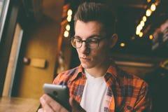 Stäng sig upp på händerna av en ung stilig man som använder smartphonen som knackar lätt på skärmen - teknologi, den sociala netw Arkivbild