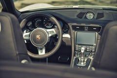 Stäng sig upp på hjulet och cockpit för styrning för bil för Porsche 911 carrera s Arkivfoto