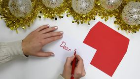 Stäng sig upp på kvinnliga händer som skrivar ett julbrev med text 'kära Jultomten ', stock video