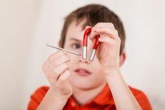 Stäng sig upp på pojken som spelar med, spikar och magneten Royaltyfri Bild