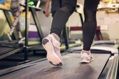 Stäng sig upp på skon, kvinnor som kör i en idrottshall på en trampkvarn Öva begrepp Kondition och sund livsstil arkivbild