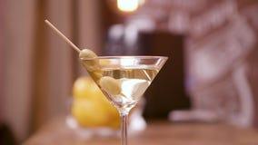 Stäng sig upp parallaxskott av ett martini exponeringsglas som garneras med oliv lager videofilmer