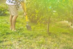 Stäng sig upp personbenarbete i trädgårds- och gräva användande skyffel s royaltyfria bilder