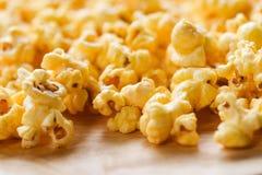 Stäng sig upp popcorn som sött smörpopcorn saltar på träbackgroubd arkivbild