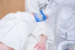 Stäng sig upp process av laser-skalning av den kvinnliga handen Laser-föryngring och hudbehandling av problematisk hud i läkarund Royaltyfri Foto