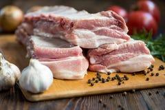 Stäng sig upp rått kött för grisköttstödet på träbräde med en krus av kryddor Arkivbilder