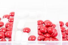Stäng sig upp röda och vita preventivpillerar i ask Royaltyfri Bild