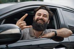 Stäng sig upp sidoståenden av den lyckliga mannen som kör bilen royaltyfri fotografi