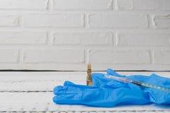 Stäng sig upp sikt över en vit trätabell med injektionssprutan, ampull och slösa handskar Influensa och säsongsbetonade sjukdomar royaltyfri fotografi