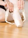 Stäng sig upp sikt av ben av ballerina som snör åt pointesna arkivfoto