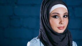 Stäng sig upp sikt av den attraktiva muslimkvinnan i hijab med den uttrycksfulla ögonkastet lager videofilmer