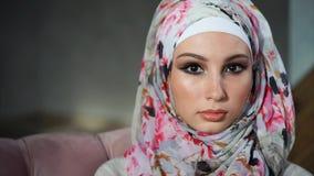 Stäng sig upp sikt av den attraktiva muslimkvinnan i ljus färgrik hijab lager videofilmer