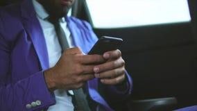 Stäng sig upp sikt av den moderna muslimaffärsmannen i bilen Honom som använder smartphonen arkivfilmer