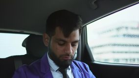Stäng sig upp sikt av den moderna muslimaffärsmannen i bilen Honom som använder smartphonen lager videofilmer