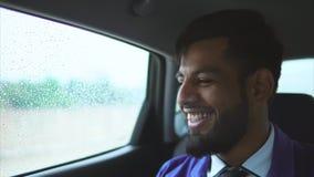 Stäng sig upp sikt av den unga muslimmannen i bilen Honom sammanträde på den bakre platsen arkivfilmer