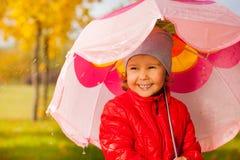 Stäng sig upp sikt av det hållande paraplyet för den gulliga lilla flickan Arkivfoton
