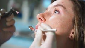 Stäng sig upp sikt av det tand- tillvägagångssättet av blekmedel Kvinnligt tålmodigt sammanträde lager videofilmer