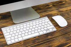 Stäng sig upp sikt av en affärsarbetsplats med datoren, trådlösa tangentbordtangenter och musen på gammalt mörker bränd trätabell Royaltyfri Foto