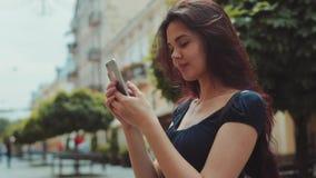 Stäng sig upp sikt av en härlig långhårig kvinna som använder hennes mobiltelefon för smsande meddelanden, medan stå i staden arkivfilmer