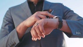 Stäng sig upp sikt av en stilig affärsman som skynda sig upp på affärsmötet, kontrolltid på hans smarta klocka i ljust lager videofilmer