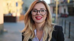 Stäng sig upp sikt av ett härligt nerdy som attraktiv blond kvinna i exponeringsglas med röda kanter som rakt till ser kameran oc lager videofilmer