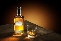 Stäng sig upp sikt av exponeringsglas med is och whisky och en flaska åt sidan Arkivbilder
