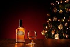 Stäng sig upp sikt av exponeringsglas med whisky på färg tillbaka själv gjord etikett Royaltyfria Bilder