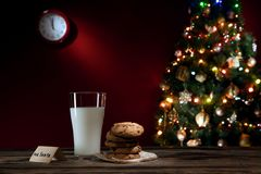 Stäng sig upp sikt av exponeringsglas av mjölkar med kakor på färg tillbaka Arkivbild
