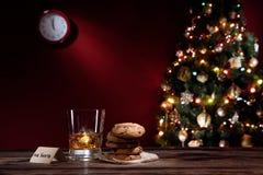 Stäng sig upp sikt av exponeringsglas av whisky med kakor på färg tillbaka Royaltyfria Bilder