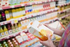 Stäng sig upp sikt av händer som rymmer fruktfruktsaft Arkivfoton