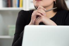 Stäng sig upp sikt av kvinnasammanträde på bärbara datorn, den hållande pennan och thinkien Royaltyfri Bild
