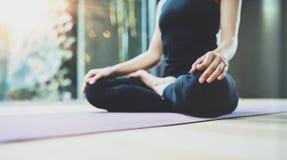 Stäng sig upp sikt av lycklig praktiserande yoga för den unga kvinnan inomhus Härlig position för flickaövningslotusblomma i grup arkivbild