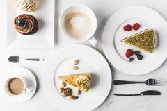 Stäng sig upp sikt av ordningen av stycken av olika kakor på plattor, koppar kaffe och muffin Royaltyfria Foton