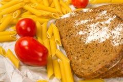 Stäng sig upp sikt av skivor av bröd som strilas med mjöl, italiensk pasta och tomater på vitbok arkivbilder