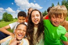 Stäng sig upp sikt av upphetsade ungar i en grupp tillsammans Royaltyfri Fotografi