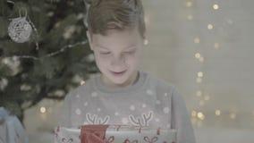 Stäng sig upp sikt på den lyckliga upphetsade asken för gåvan för gåva för jul för ungepojkeöppningen som förvånas i vördnad som  stock video
