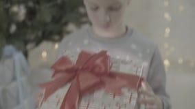 Stäng sig upp sikt på för pojkeöppningen för den upphetsade ungen som den lyckliga asken för gåvan för gåva för jul förvånas i vö arkivfilmer