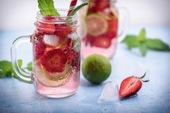 Stäng sig upp sikt på limefrukt- och jordgubbedetoxdrinken i glass murarekrus på en blå bakgrund 8 arkivfoton