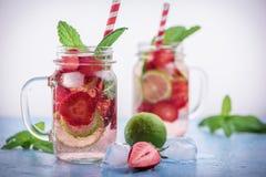 Stäng sig upp sikt på limefrukt- och jordgubbedetoxdrinken i glass murarekrus på en blå bakgrund 12 Arkivbild