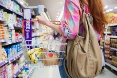 Stäng sig upp sikten av kvinnan som gör livsmedelsbutikshopping med shoppingkorgen royaltyfri fotografi