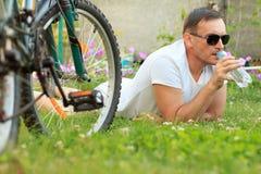 Stäng sig upp sikten av mannen som ligger på grönt gräs och dricksvatten för Royaltyfri Foto