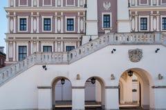 Stäng sig upp sikten av stadshuset, välva sig och moment i den historiska stora marknadsfyrkanten i Zamosc Polen royaltyfri fotografi